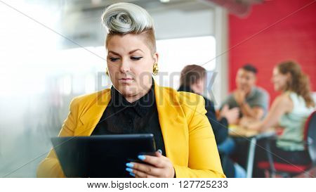 Casual portrait of a business woman using technology in a bright and sunny startup with the team in the background