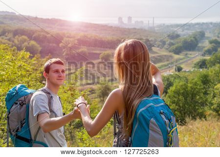 Girlfriend and Boyfriend Couple with Backpacks on Green Forest Background Holding Hands Leading Smiling rising Sun on Background