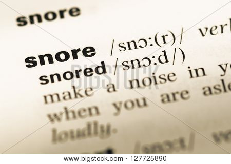 Close Up Of Old English Dictionary Page With Word Snore.
