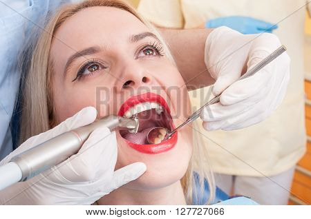 Dental drilling procedure on perfect woman teeth smile or denture