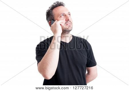 Modern man thinking while talking on smartphone and looking up like a visionary male