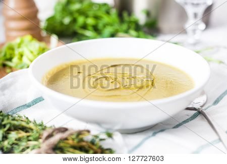 A close up photograph of a white bowl with classic vegetarian potato and leek soup decorated with olive oil. Green parsley, wood peppermill and sliced leek on background. White rustic wood background