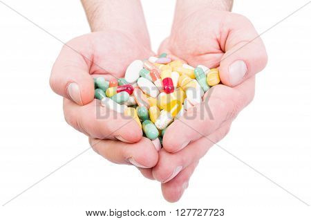 Both hands holding bunch of pills. Overdose or abuse concept on white background
