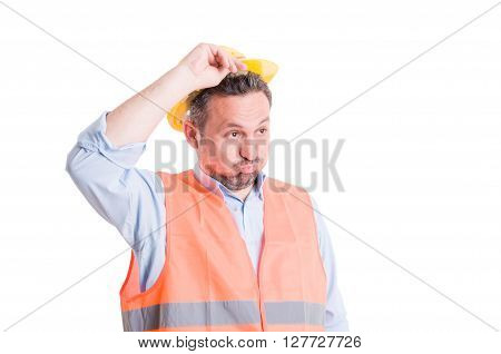 Shocked tired or surprised worker or chef engineer lifting his yellow helmet