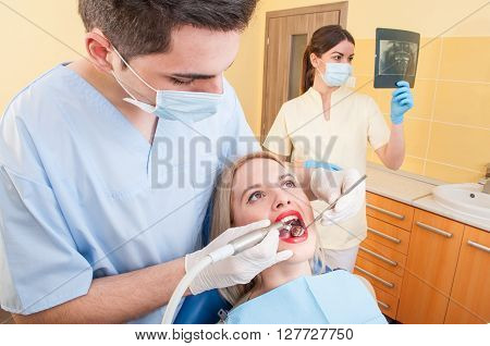 Beautiful woman patient in dentist office or cabinet getting her teeth checked by the young doctor