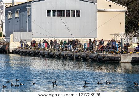 Sochi, Russia - February 9, 2016: Many anglers are fishing from the pier in the sea port of Sochi
