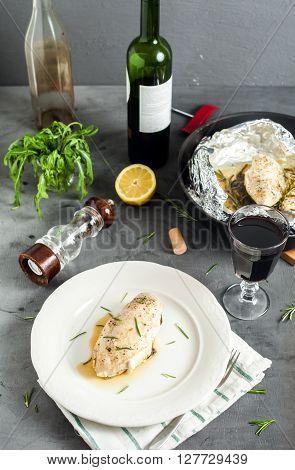 Steamed in foil chicken breast with rosemary and spinach. Served with red wine. Grey stone background with glass, bottle, pepper mill and black pan with chicken.