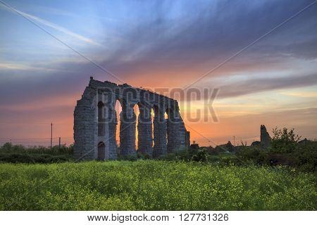 In a park on the outskirts of Rome it stands the ruins of a great aqueduct built in Roman times. In the spring scene is taken at dusk behind a field of yellow flowers.
