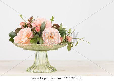 Fresh cut pink garden roses arranged in a glass pedestal vase in horizontal format.