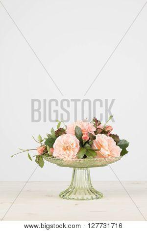 Fresh cut pink garden roses arranged in a green glass pedestal vase in vertical format.