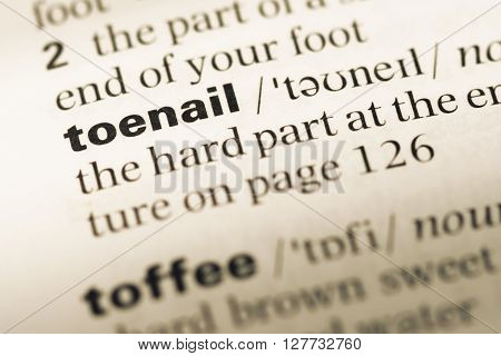 Close Up Of Old English Dictionary Page With Word Toenail.