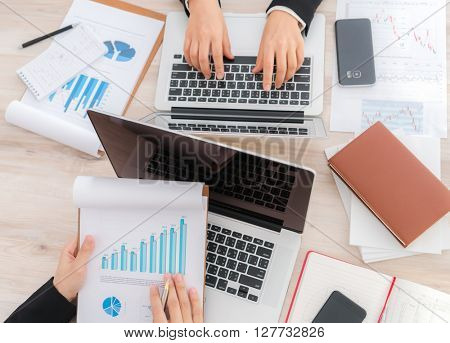 Business people using laptop  and Financial charts  at meeting office