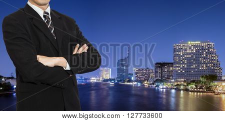 One business man wear black suit stand on modern building in night light background