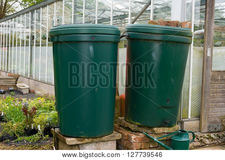 Two green water butts outside a greenhouse being used for water storage