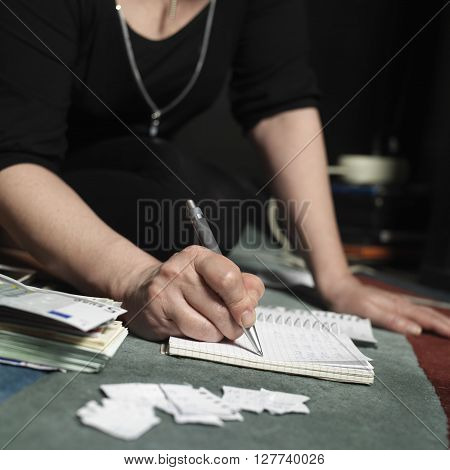 Female hands making some calculations in a notepad next to a pile of Euros and torn pieces of paper in the blurred foreground