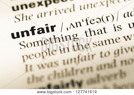 Close Up Of Old English Dictionary Page With Word Unfair.