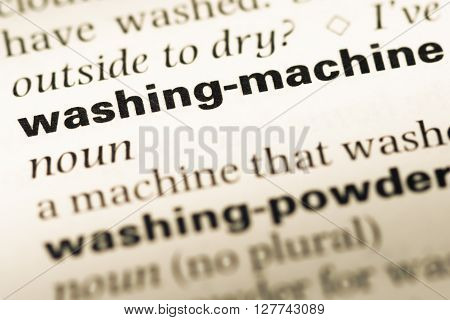 Close Up Of Old English Dictionary Page With Word Washing Machine.