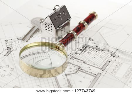 key with keychain in the form of a silver-colored house on a background of architectural drawing &  magnifying glass
