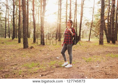 Beautiful young hipster girl in a red plaid shirt and leather backpack in the forest among the pine trees with sun on background