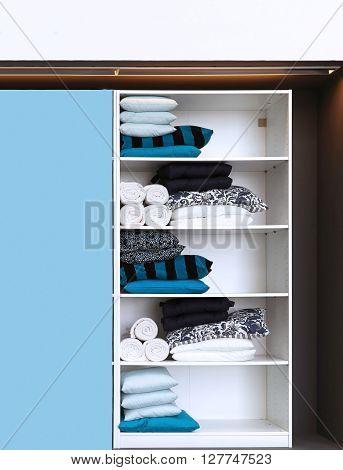 Open closet with blue color home decor textile on shelves