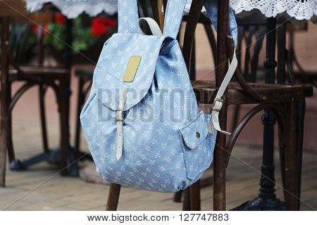 backpack hanging on the back of a chair cafe