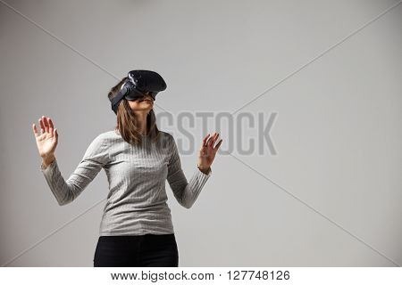 Woman Watching Television Wearing Virtual Reality Headset