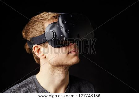 Young Man Wearing Virtual Reality Headset In Studio