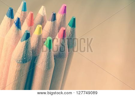 Color Pencils on wooden background with color effect