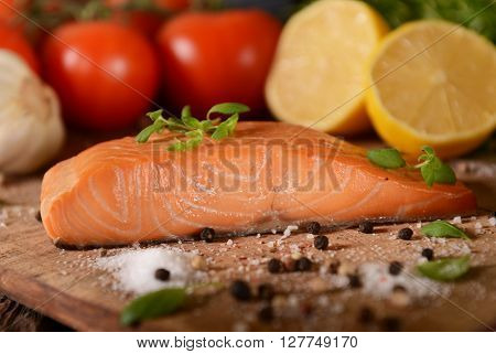Smoked salmon slice with pepper on wooden board