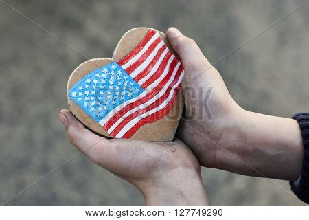 young homeless boy holding a American Heart Flag dirty hand