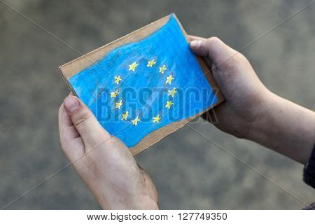 young homeless boy holding European Union flag painted on paper dirty hand