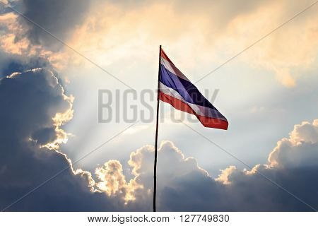 Thai nation flag on wooden pole with sunbeam and cloud