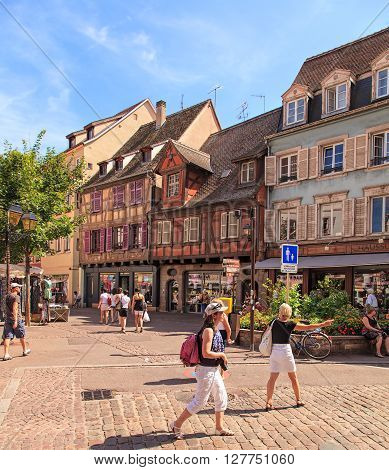 Colmar, France - 18 July, 2014: stores and people in the old town. Colmar is the third-largest commune of the Alsace region in north-eastern France renowned for its well preserved old town, numerous architectural landmarks and museums.