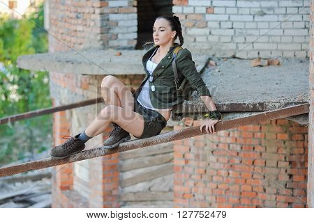 Girl near the brick wall in military style.