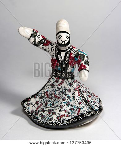 Souvenir statuette of ceramics. Statuette depicts a dancing dervish in torque. In the suit floral ornament.