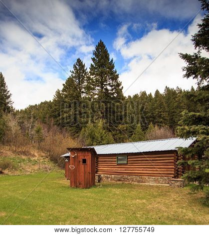 Log cabin and rustic outhouse in a forest in Montana.