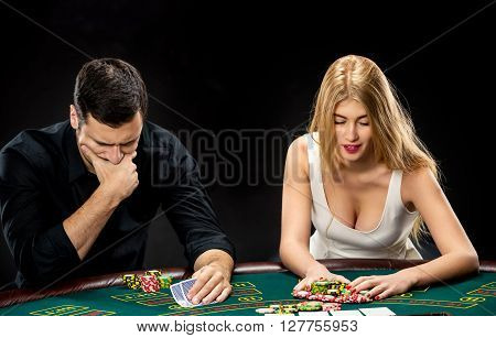 Two poker players sitting at a poker table on black background and going all-in pushing his chips forward