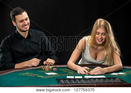 Young couple playing poker and have a good time in casino, woman taking poker chips after winning