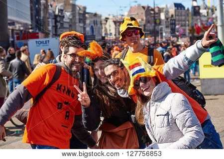 AMSTERDAM, NETHERLANDS on APRIL 26, 2015. City natives and tourists group portrait during celebration Queen's Day or King's day, Dutch annual national holiday, in  Amsterdam, Holland