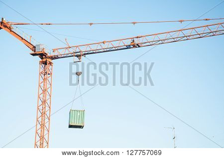 Crane at a construction site with a container suspendeditaly