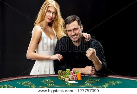 Young couple playing poker and have a good time in casino. Man taking poker chips after winning, woman embracing his