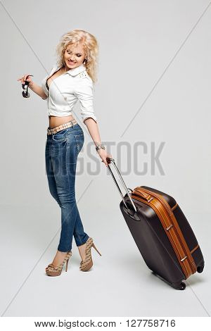 Beautiful woman tourist going on vacation, a suitcase full of things, wearing a leather jacket and blue jeans, high-heeled shoes, sunglasses