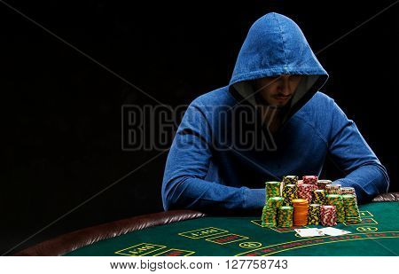 Poker player sitting at poker table with chips table trying to hide his expressions and looking combination of two aces.