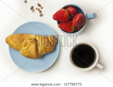 A photo of a healthy breakfast: a cup of coffee a mug with fresh strawberries and a fresh croissant with some cane sugar pieces in the background shot from above on white background
