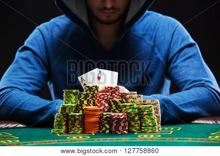 Poker player sitting at a poker table with chips and showing a pair of aces. Closeup