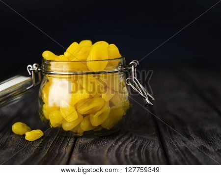 little dried yellow kumquat in glass jar om wooden table