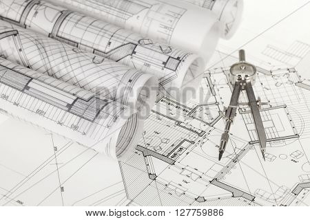 rolls of architecture blueprints, house plans &  compass