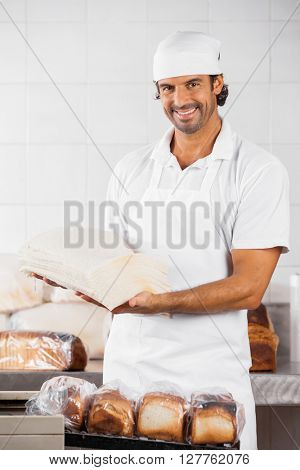 Male Baker Holding Bread Slices In Bakery