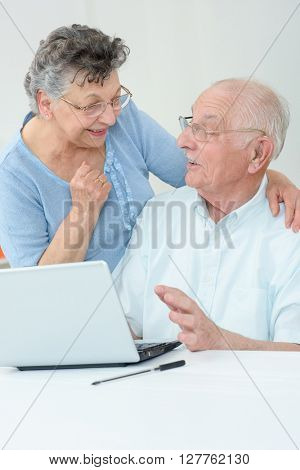 elderly couple in front of a laptop