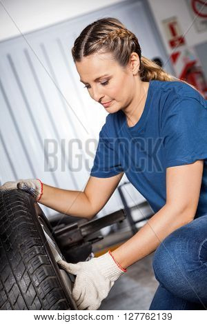Female Mechanic Examining Car Tire